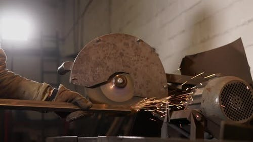 Laborer Is Sharpening an Edge of Metal Billet By Industrial Rotating Polisher