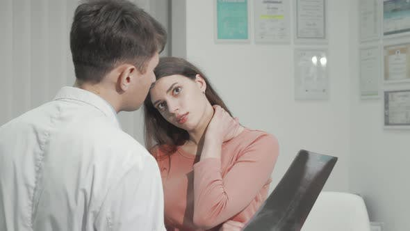 Woman with Neck Pain Talking to Her Doctor After Xray Scanning
