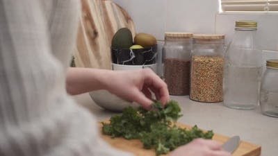 Female Hands Putting Salad Into a Salad Bowl