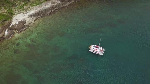 Stylish Boat Catamaran Drifts on Tranquil Azure Sea at Beach