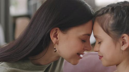 Loving Mom And Daughter Touching Foreheads