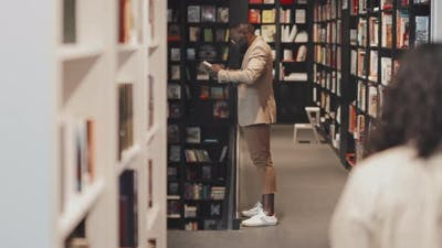 African American Man Reading Book in Library