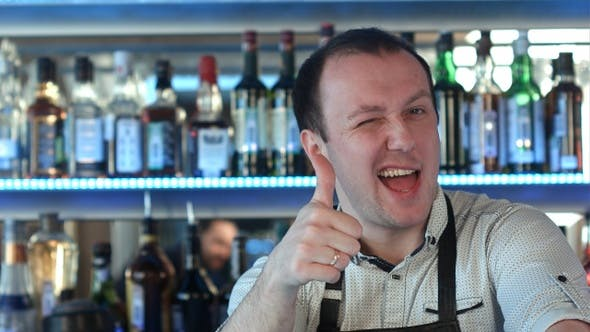 Thumbnail for Bartender standing at the counter smiling showing his thumb up