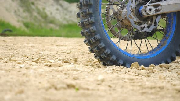 Close Up Wheel of Powerful Off-road Motorcycle Spinning and Kicking Up Dry Ground or Dust