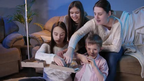 Big Family Eating Pizza and Taking Slices From Box While Watching TV Show or Movie in Living Room