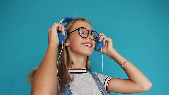 Cover Image for Teenage Girl with Long Hair in Glasses Putting on the Headphones Listening to Music