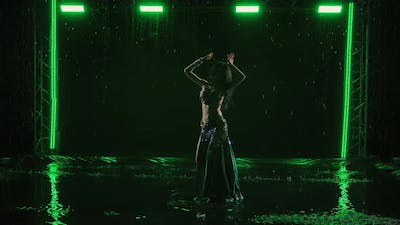 Exotic Oriental Dancer is Silhouetted Dancing Belly Dance on Surface of Water Among Raindrops in
