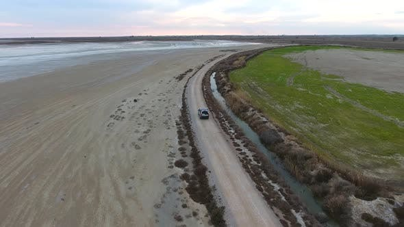 Thumbnail for Car Going on Dirt Road on Sandy Waterside