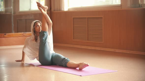 Thumbnail for Young Woman Warming Up Sitting on the Yoga Mat and Doing Leg Stretching Exercises - Dance Studio