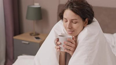 Woman Enjoying Coffee in Bed