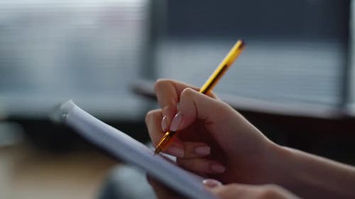Closeup Hands of Unrecognizable Woman Making Notes in Paper Notebook with Pen Sitting on Chair on