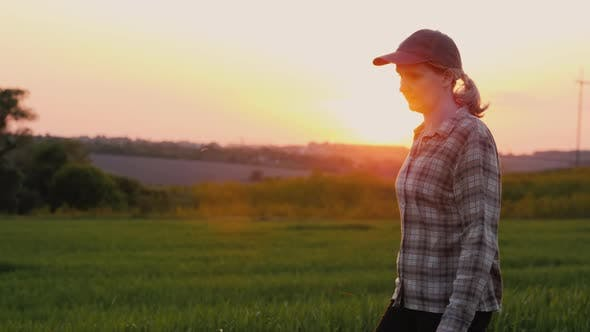 Thumbnail for Side View: A Female Farmer Walks Through a Picturesque Field at Sunset
