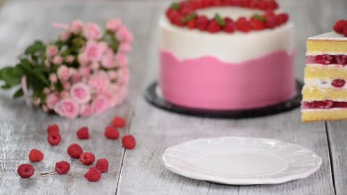 Piece of delicious raspberry cake with fresh raspberries.