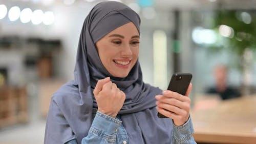 Arab Woman Celebrating Success on Smartphone