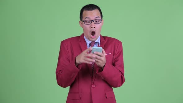 Cover Image for Happy Asian Businessman Using Phone and Looking Surprised