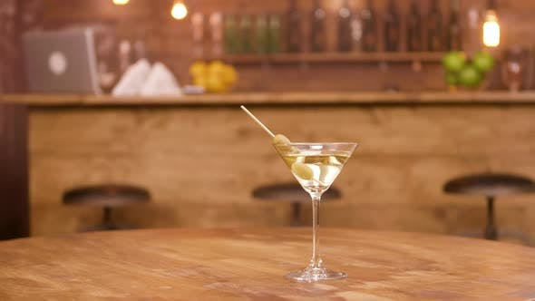 Parallax Shot of a Martini Glass on an Empty Wooden Table with Bar Counter on the Background