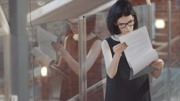 Thumbnail for Intelligent Businesswoman Reading Agreement in Office