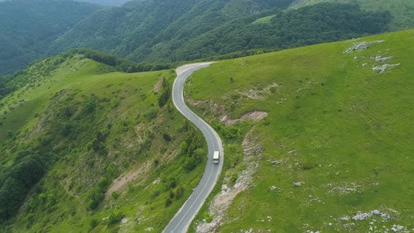 A Car Going Trough a Winding Road High in The Mountains