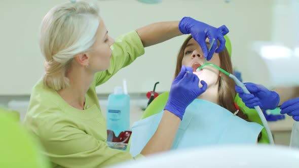Dentist Examining Patient Teeth with Dental Tools Doctor and Patient