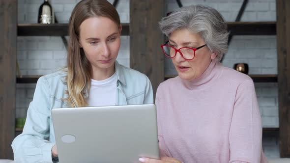 Thumbnail for Happy Two Age Generation of Women. An Older Mother and an Adult Daughter Have Fun Using a Laptop at
