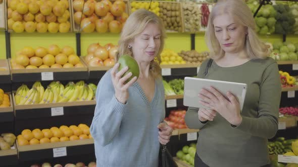 Thumbnail for Confident Blond Caucasian Woman with Tablet Advising Female Friend Choice of Best Fruit in Grocery