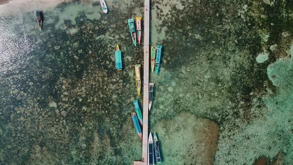 Luftaufnahme des Bildes von oben nach unten von bunten Holzbooten. Boote am Pier und Lärmwolke