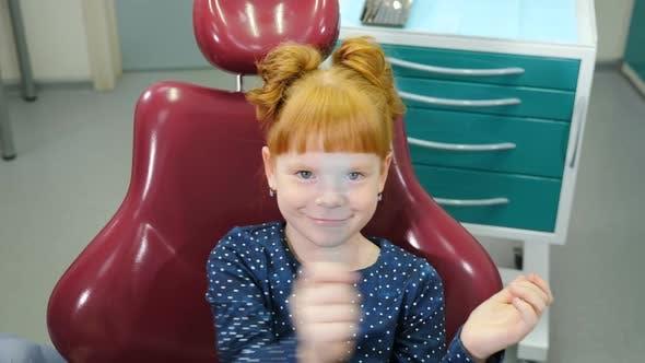 Thumbnail for Pediatric Dentistry Concept. Charming Little Girl in Dental Chair. Lovely Red-haired Girl Having Fun