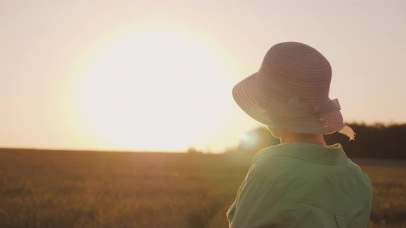 Thumbnail for A Female Farmer in a Hat Looks at the Horizon Above a Field of Wheat