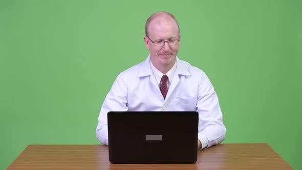 Thumbnail for Stressed Mature Bald Man Doctor Arguing To the Laptop Against Wooden Table