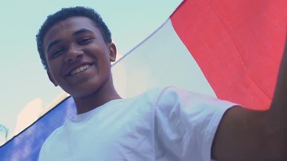 African-american teenage boy waving French flag, sports fan