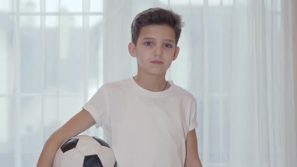 Thumbnail for Close-up Portrait of Smiling Caucasian Brunette Boy Standing with Football Ball