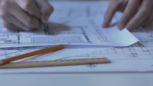 Thumbnail for Male architect checking building layout, making notes and calculations, design