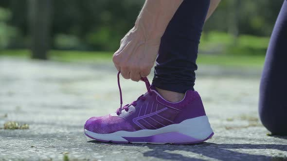Thumbnail for Young Female Leg and Hands Tying Laces on Running Shoe
