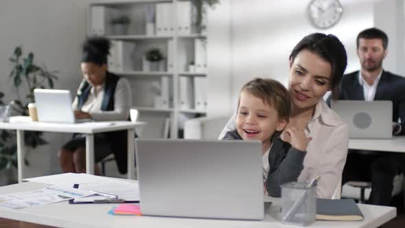 Cover Image for Businesswoman Watching Cartoon on Laptop with Child on Knees
