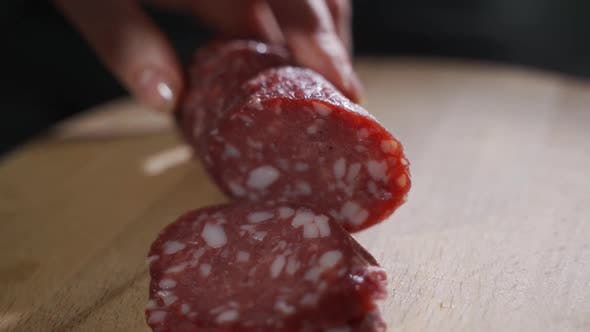 Cover Image for Man Cuts Into Thin Slices Fatty Sausage. Shooting Closeup. Chef Cutting Salami with a Knife