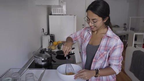 Smiling Brunette Woman in Eyeglasses Whiskering Eggs at Kitchen.
