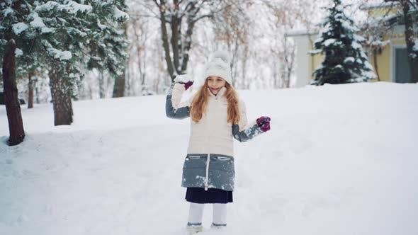 Девушка красоты в теплой пуховике и шляпе держит снежок в руке и бросает его вперёд