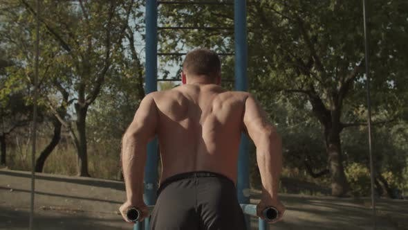 Thumbnail for Fit Man Doing Tricep Dips on Parallel Bars Outdoors
