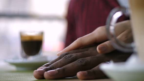 Thumbnail for Woman's Hand Covering Dark-skinned Man's Hand