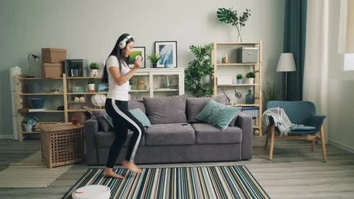 Asian Young Lady Is Enjoyig Modern Technology Listening To Music in Wireless Headphones and Dancing