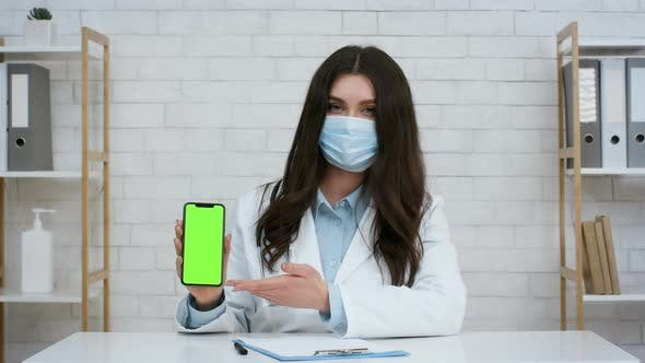 Female Doctor Showing Smartphone With Blank Green Screen In Clinic
