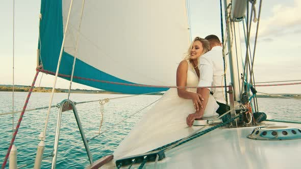 The Newlyweds Are Sailing on the Lake Aboard the Yacht. The Bride with Closed Strokes the Hand of