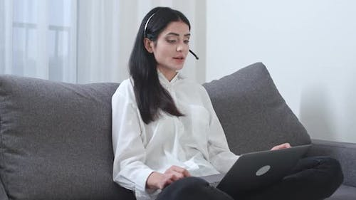 Female Freelancer Sitting on the Couch and Working on a Laptop Video Call Female Work in Technical