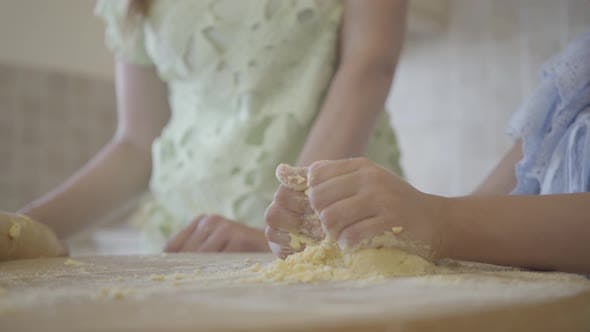 Thumbnail for Hands of the Little Girl Kneading the Dough While Her Mother Standing Near