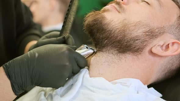 Barber Hands Hold Special Tool and Trim Customer Beard