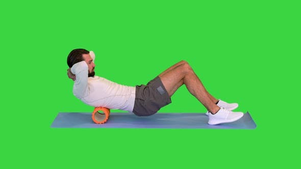 Athlete Massaging Upper Back Muscles with Foam Roller on a Green Screen Chroma Key
