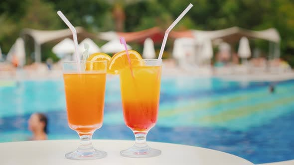Thumbnail for Two Exotic Cocktails on the Background of Bathing Tourists in the Pool in a Large Comfortable Hotel