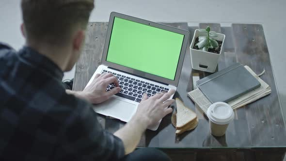 Cover Image for Man Working on Laptop with Chroma Key Screen