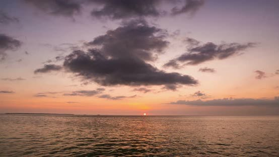 Thumbnail for Time lapse: sunset over tropical sea colorful dramatic sky moving clouds. Kei Is