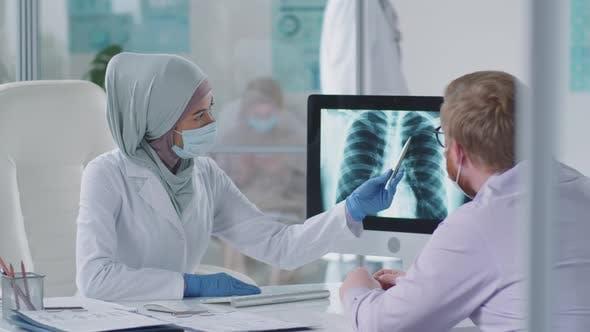 Muslimische Ärztin in Maske erklärt dem Menschen Röntgen